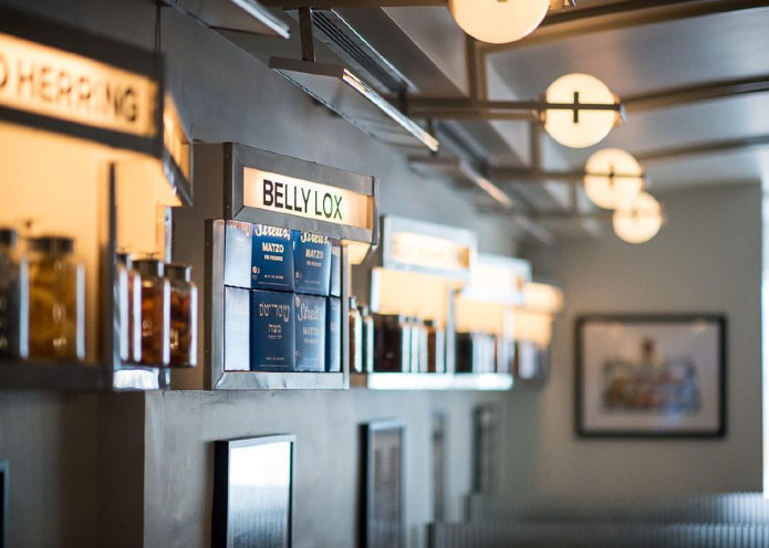 The backlit pharmaceutical inspired signs hanging above tables and booths pair perfectly with the sconces hanging high above.