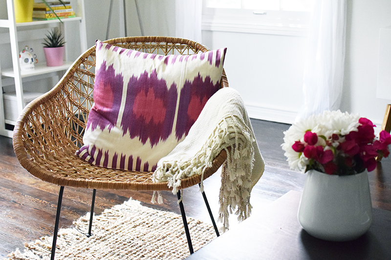 This wicker chair is a perfect example of something that' not over-the-top boho and will compliment traditional furniture but can be dressed up with boho Ikat-style throw throw pillows and blankets.