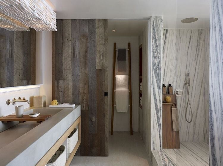 Bathrooms are large with concrete dual vanity sinks, marble showers, and vanity lights covered by white washed branches.