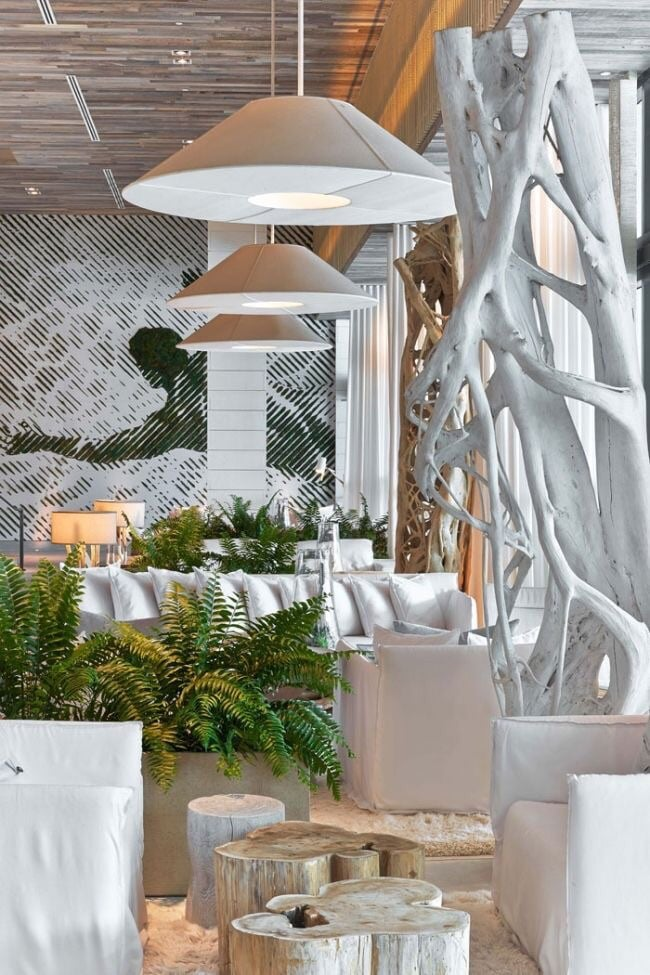 For guests looking to spend time outside their room and away from the humidity, the waiting area at the 1 Hotel South Beach is perfectly inviting with wood stump tables and lush green ferns.
