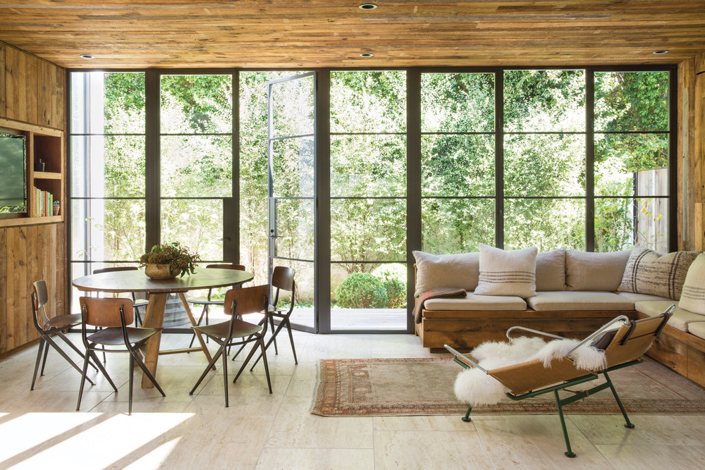 The large industrial steel-framed windows let in so much light, it might as well be a greenhouse.  It really helps to refine the natural features found in the informal dining room.