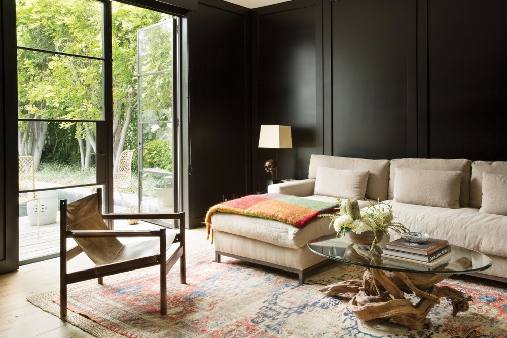 The dark paneled walls perfectly match the industrial black steel framed windows in this Beverly Hills living room.  To contrast, the Oushak rug and tree branch coffee table base add warmth and character.