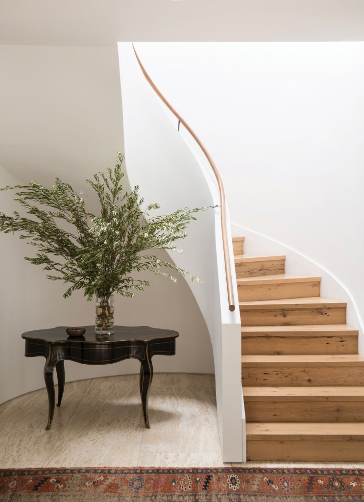 The Persian rug in the bottom of this stairway provides character and charm to an otherwise sparsely decorate area.
