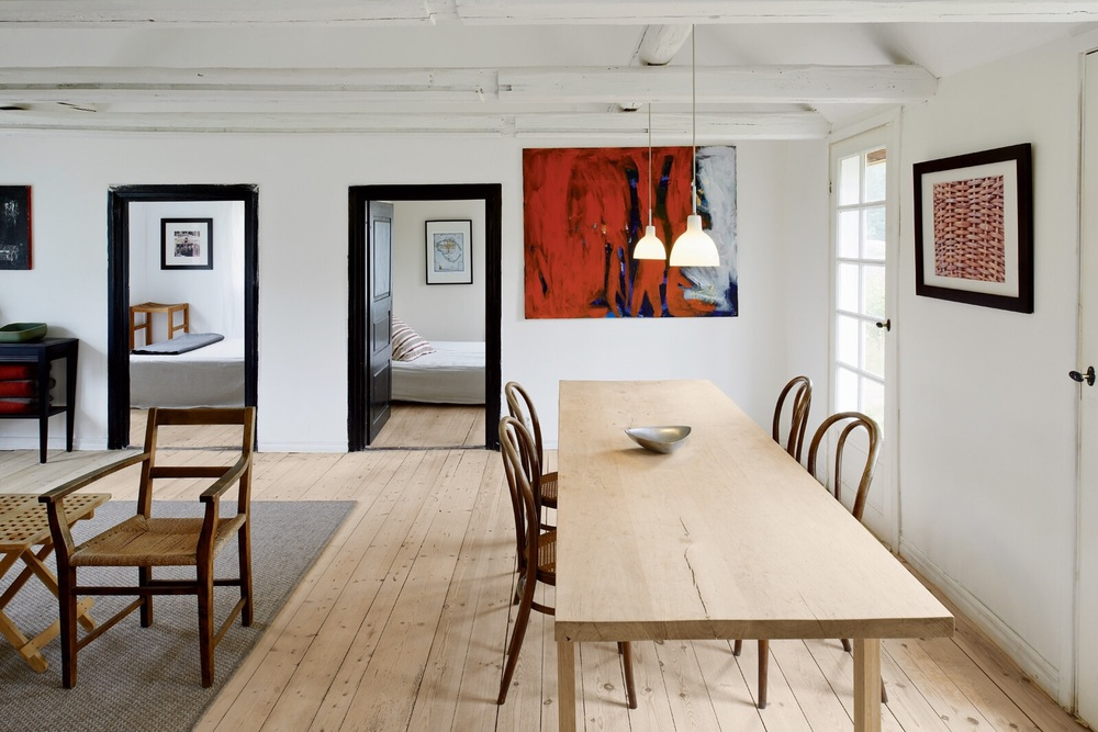 A long dining table is sparsely decorate with only four dining chairs to create scale.