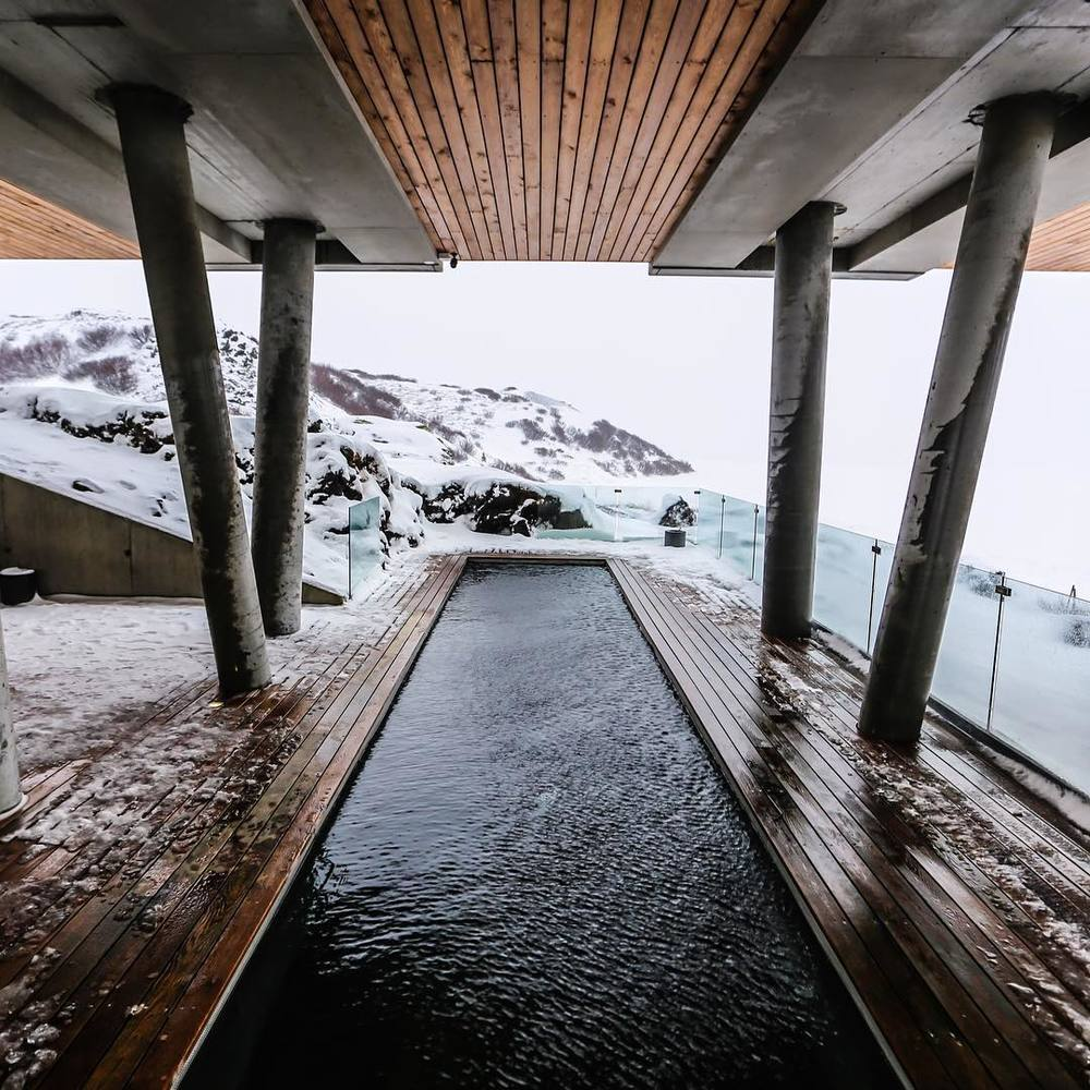 Pool deck overlooking snowcapped mountainscape at Ion Adventure Luxury Hotel by Design Hotels in Iceland.