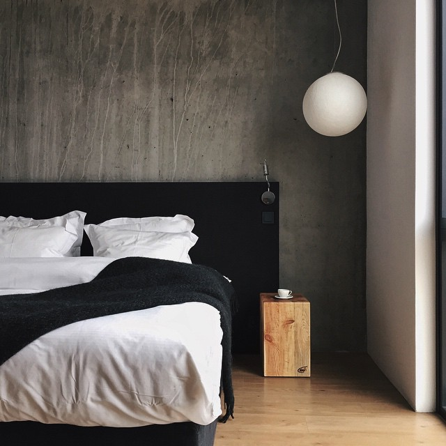 Hotel rooms at the Ion Adventure Luxury Hotel have a beautiful minimalist approach with concrete walls, globe pendant lights, and a simple square log nightstand.