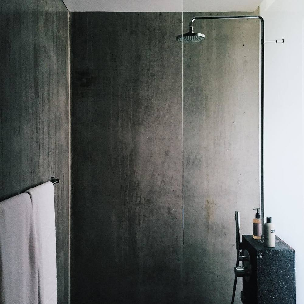 The slate tile in the bathroom shower matches the minimalist design found throughout the Ion Adventure Luxury Hotel