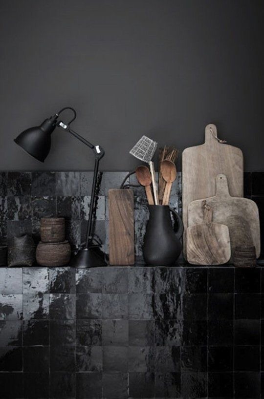The pearlescent gloss of these Moroccan Zellige tiles make this black kitchen feel a lot more light.  I love how it's also paired with muted neutral butcher blocks.
