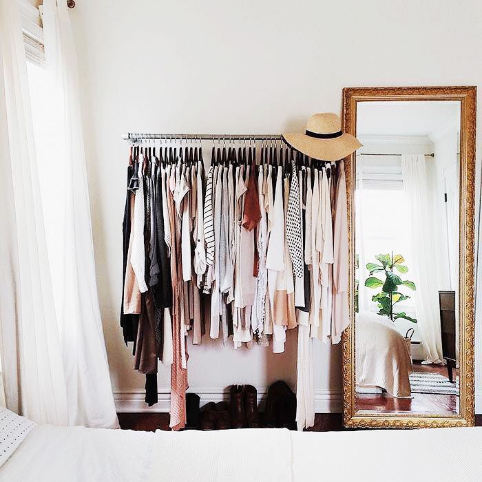 Style open closets with a cute hat at the end and next to a brass-framed leaning floor mirror.