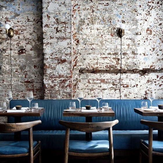 White washed brick walls and blue Danish chairs and benches create an inviting restaurant experience.  Minimalist brass sconce lights give it a romantic charm.