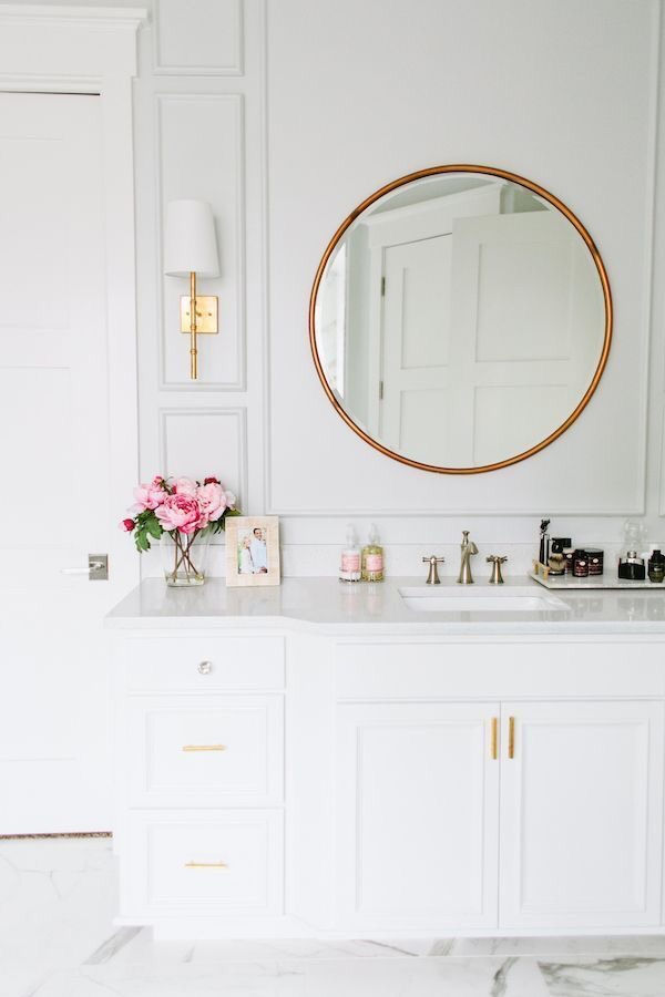 This white and gold bathroom is so cute, sophisticated, and feminine.  I love the touch of pink peonies.