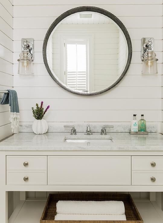 This traditional bathroom with shiplap walls and clear glass sconces is perfect for a Cape Cod-inspired home.  I love the touch of Molton Brown products and the turkish towels.