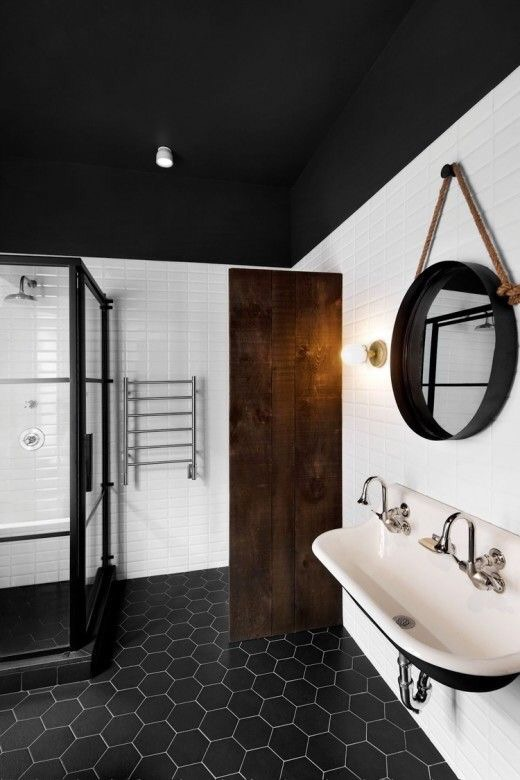 The masculine touch of black honeycomb tile and a steel framed round mirror are softened with rustic features.
