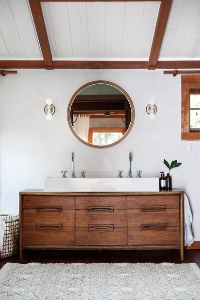 The wood beams in this rustic bathroom really bring out the neutral tones in the frame of the round mirror.