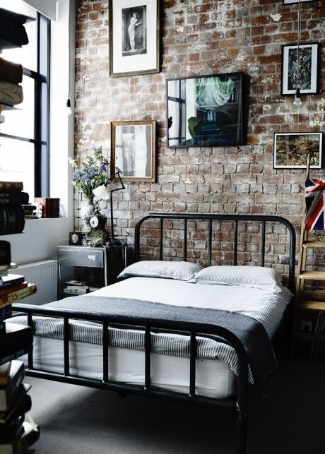 A minimalist black wrought iron bed helps to make the charm of an exposed brick wall pop.