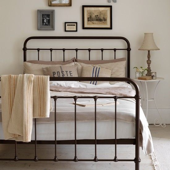 The rustic appeal of this bronze wrought iron bed with burlap inspired pillows is too cute!