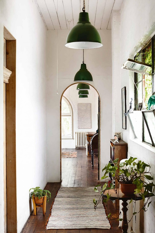The rustic beauty of this green pendant light entryway accented with lush green plants.
