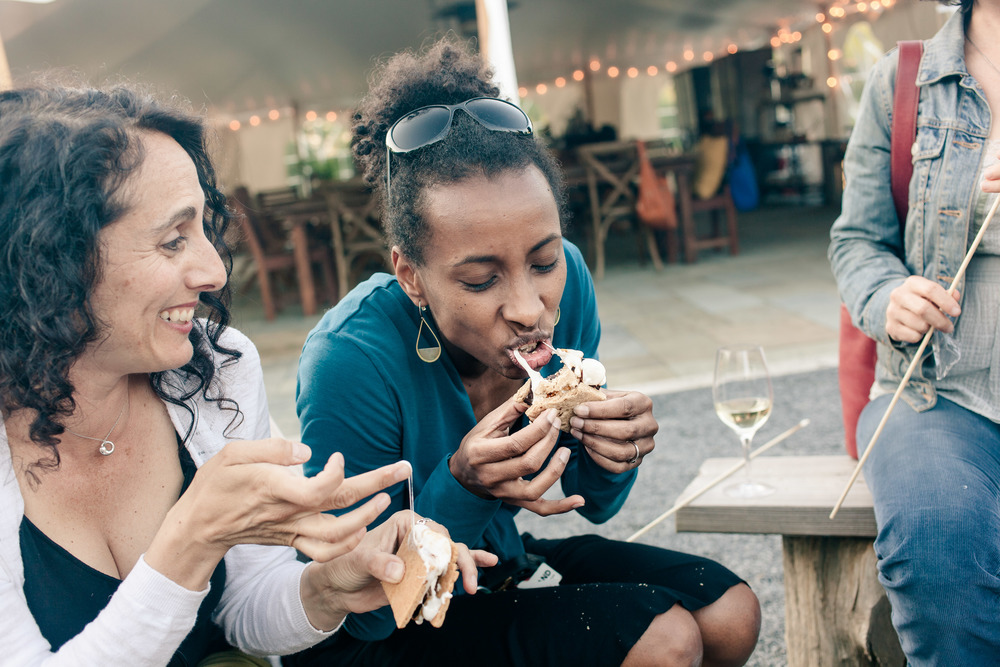 I love this picture of our friend Zainab digging into a s'more, with Gina right behind her! Photo by  Allison Usavage