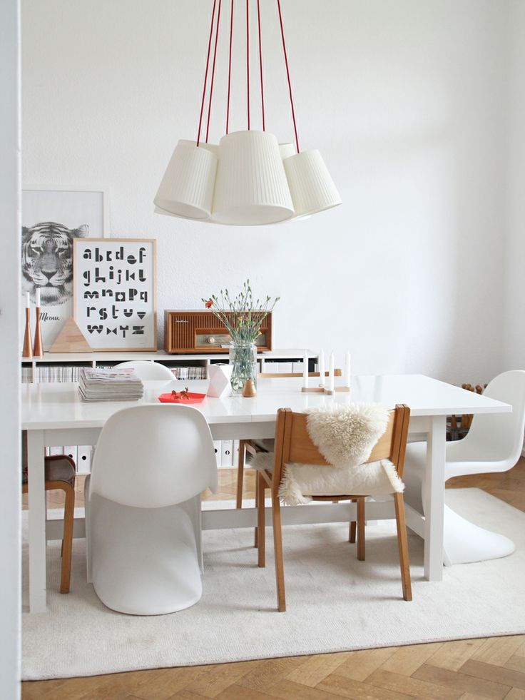 Graphic art + mix of chairs + that gorgeous pendant light + a white rug where you eat = playful place to dine.