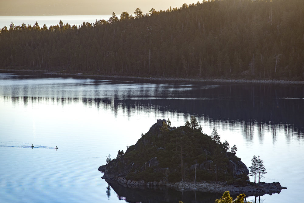 Paddle boarders slip through the glassy waters of Emerald Bay, Lake Tahoe.