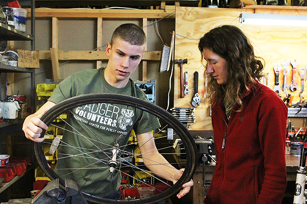 Badger volunteers Tim Koll and Michelle Duren inspect a wheel while volunteering at Wheels for Winners.