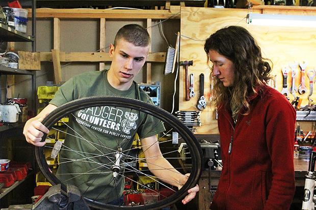 Badger volunteers Tim Koll and Michelle Duren inspect a wheel while volunteering at Wheels for Winners.