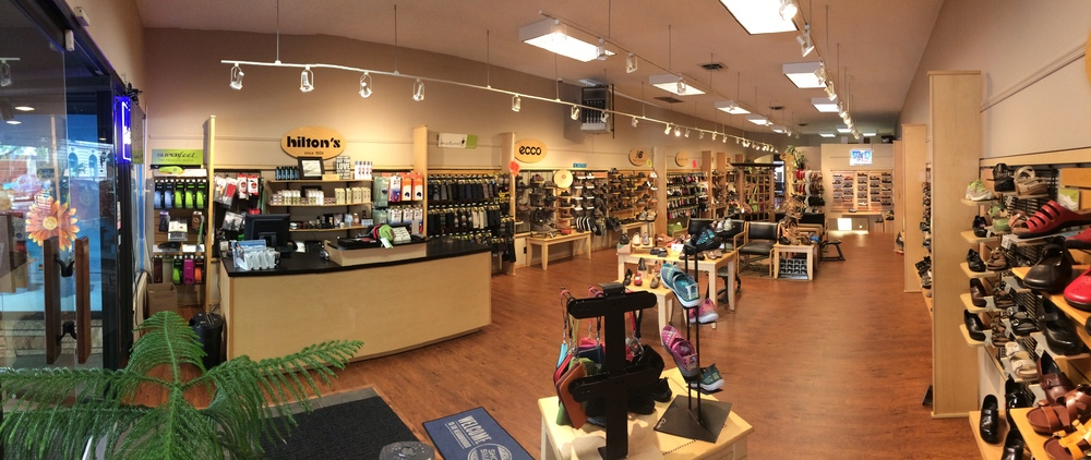 The store entrance and service counter. Men's shoes are on the far wall and women's shoes are on the near wall.
