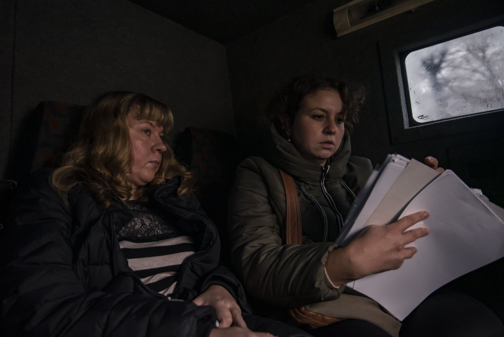 Irina Shopina (left) and Veronika Korol of ICF Res.Publica, a Kyiv-based volunteer group, check their patient lists before delivering medical aid to elderly in the front line town of Avdiivka, Ukraine.
