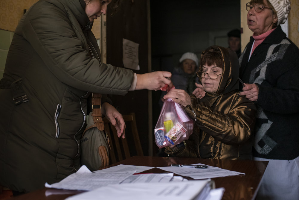 Veronika Korol of ICF Res.Publica, a Kyiv-based volunteer group, hands over a bag of medicines to a woman at the hospital in Avdiivka.