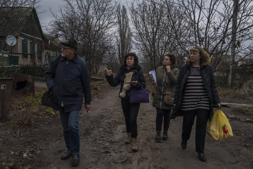 Kyiv-based voulnteers Ksenia Ponomarjova, Irina Shopina, and Veronika Korol look for the home of an elderly woman with local doctor Dr. Sergei Yakovlevich in Avdiivka, Ukraine.