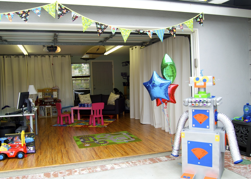 Utilizing our garage for the Robot Party.  We also usually have a bounce house set up in the front yard, along with a tent and a couple of tables  on  the driveway.  We live on a cul-de-sac and we park our cars in front of the driveway, so this works for us!