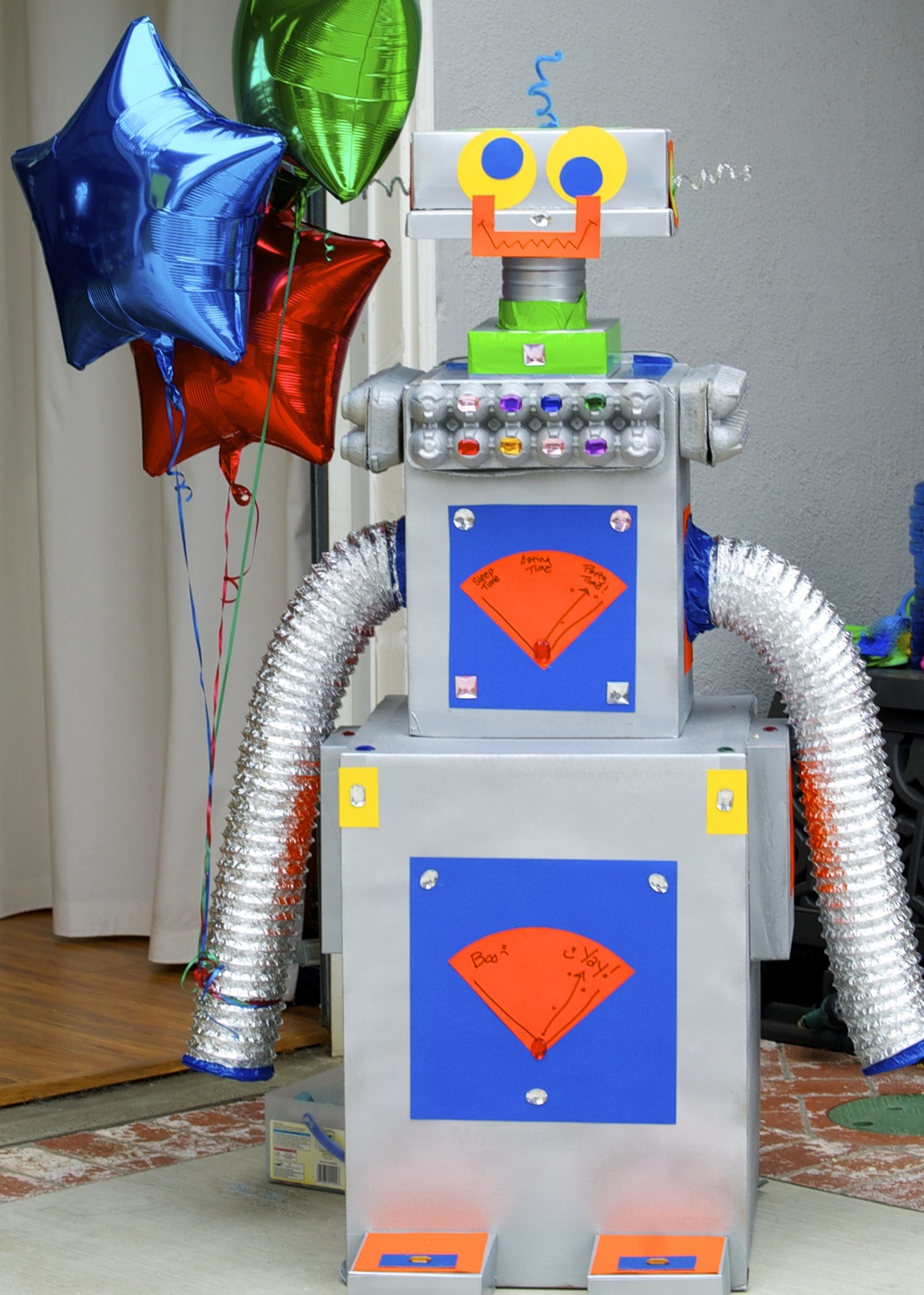 Making these robots was a blast. I purchased some large moving boxes from Home Depot and then added some smaller boxes we had saved, along with some dryer duct.  Some silver metallic spray paint, colored paper, and other bits and bobs were all this robot needed for the  Robot Party !