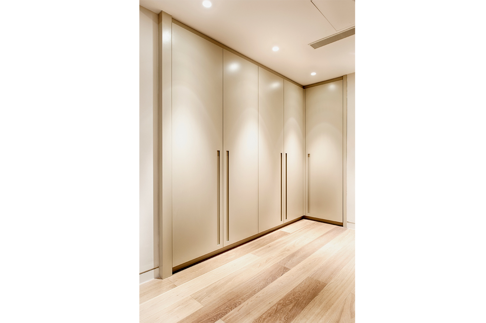 Courtfield Gardens – an L-shaped wardrobe with recessed handles and en-suite area in dark walnut