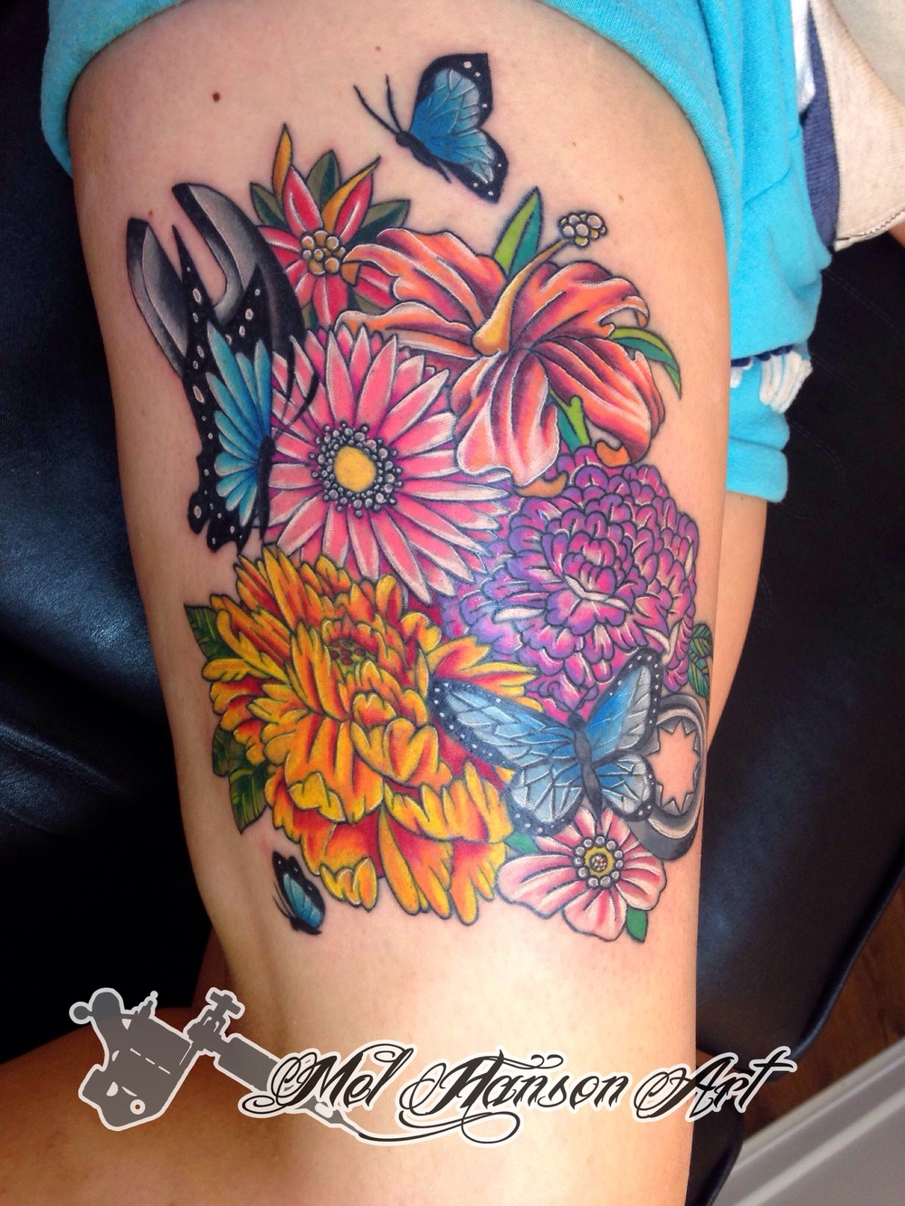 colourful spanner and flowers thigh tattoo