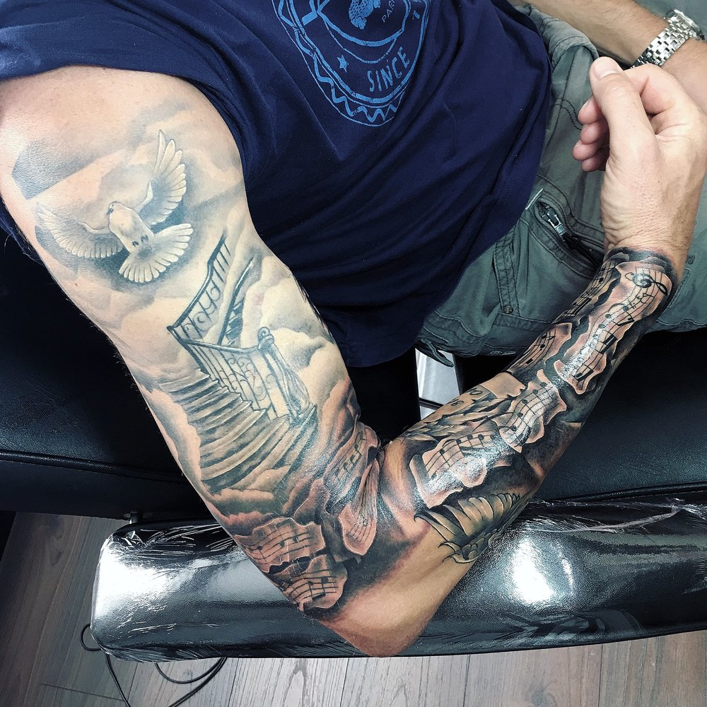 black and grey religious sleeve tattoo by mel hanson