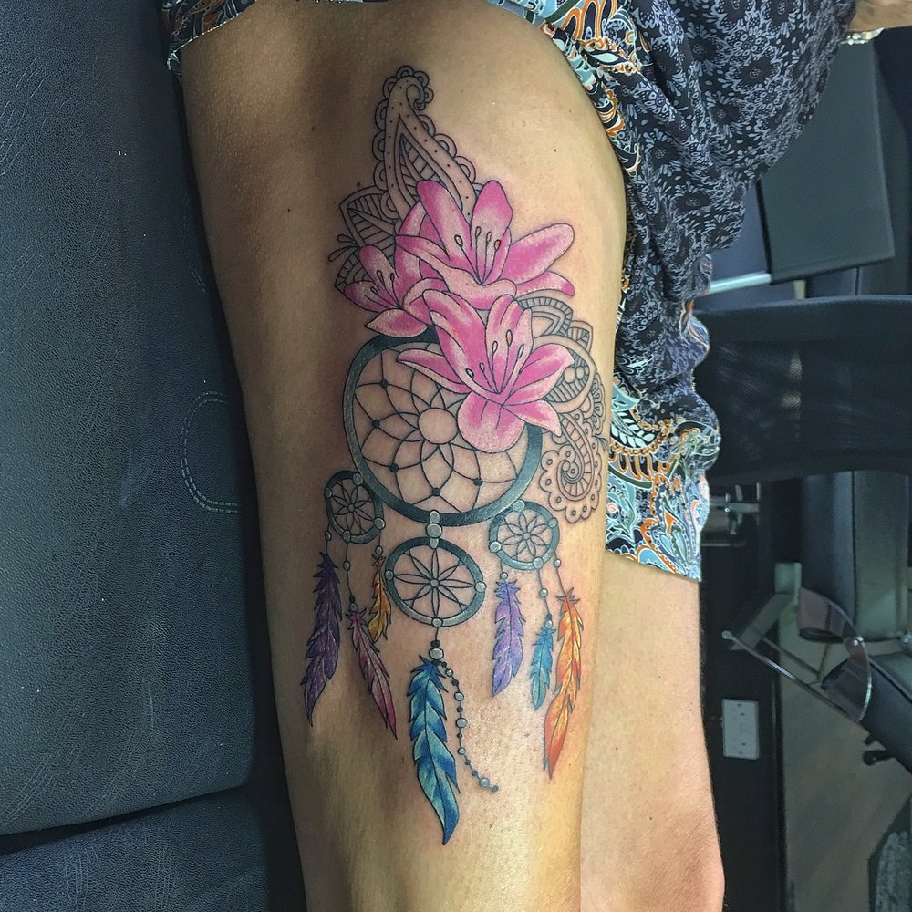 colourful dreamcatch tattoo on the thigh by mel hanson