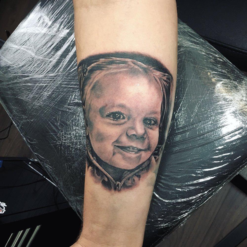 child black and grey portrait tattoo by mel hanson