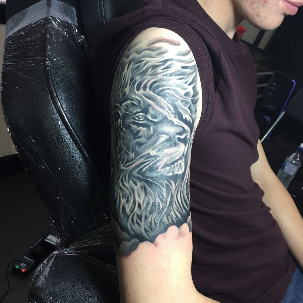 black and grey lion with clouds sleeve tattoo by mel hanson