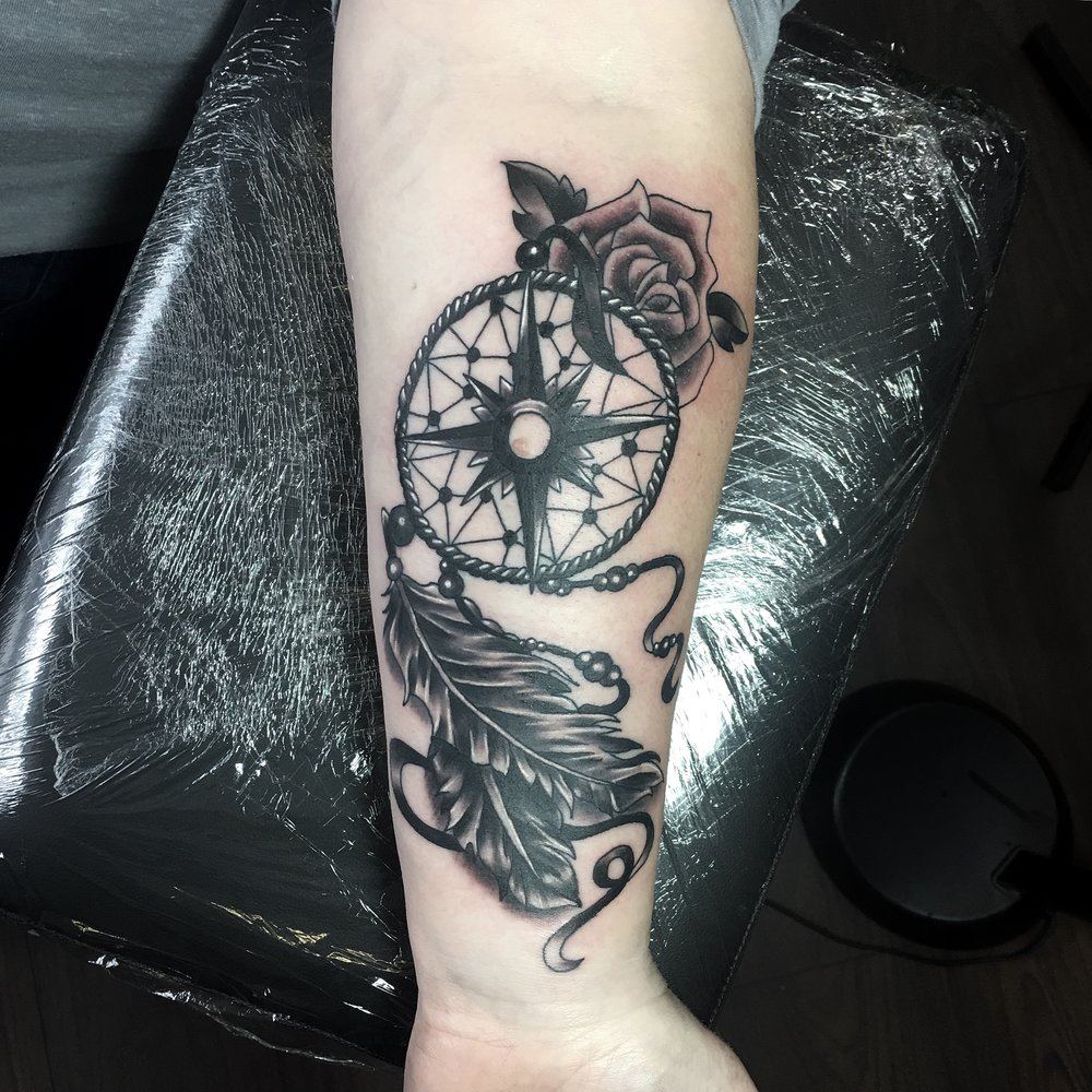 black and grey dreamcacther with compass feathers rose beads tattoo by mel hanson