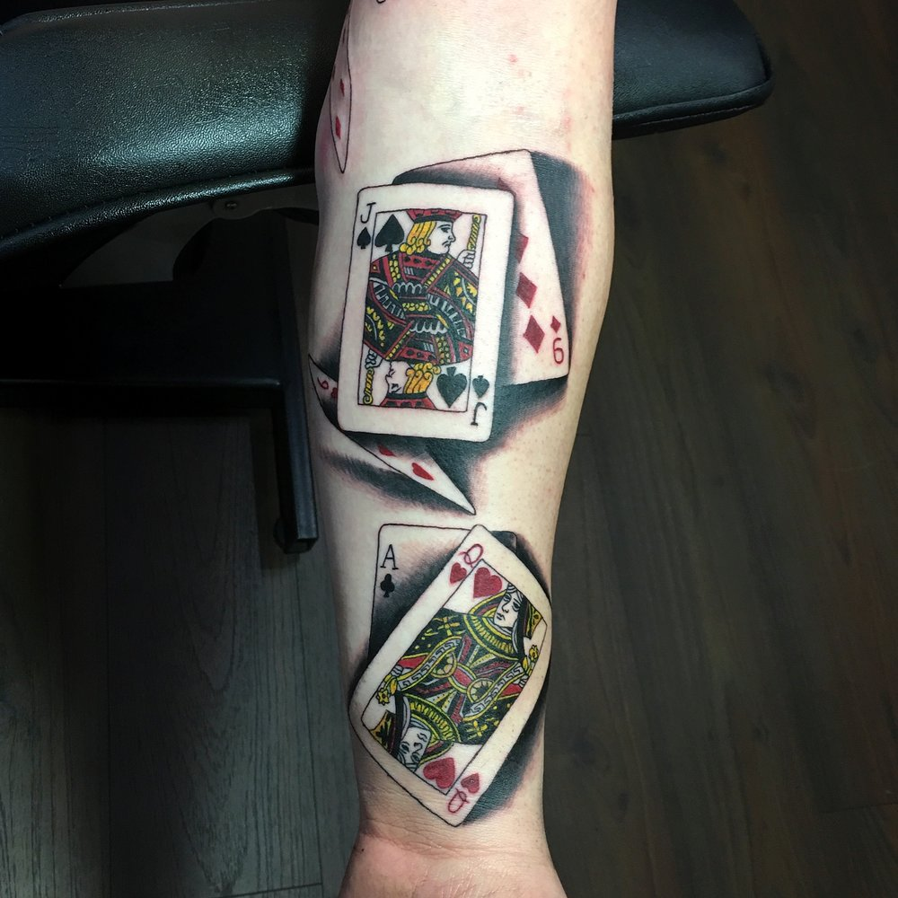 black and grey with red and yellow playing cards tattoo jack of spades and queen of hearts realistic cards on sleeve by Mel Hanson at Mel's Tattoo Studio, in Sittingbourne, Kent, UK