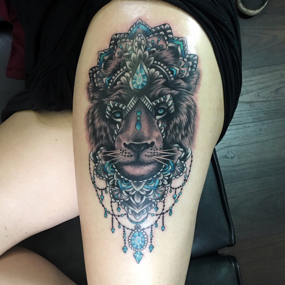 Black and grey lion head with mandala and hanging jewels with blue and turquoise highlights by Mel Hanson at Mel's Tattoo Studio, Sittingbourne, Kent UK