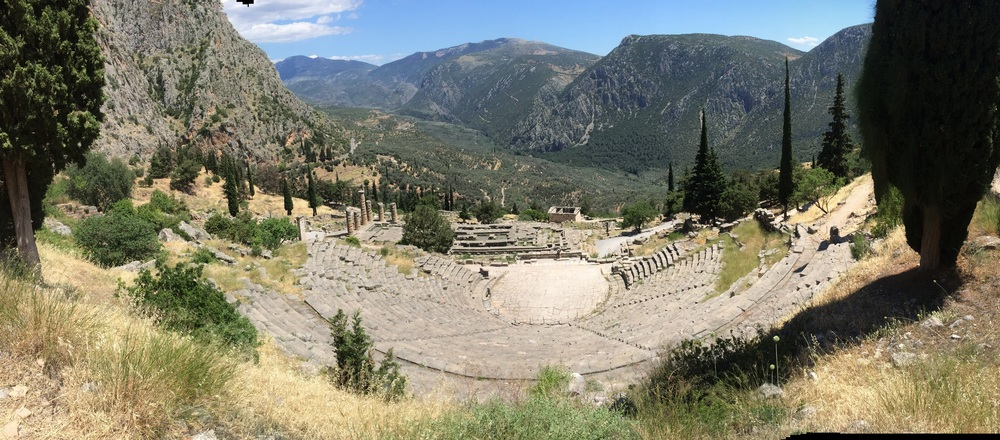 Delphi theater with Apollo Temple and Treasury of Athens in the back.
