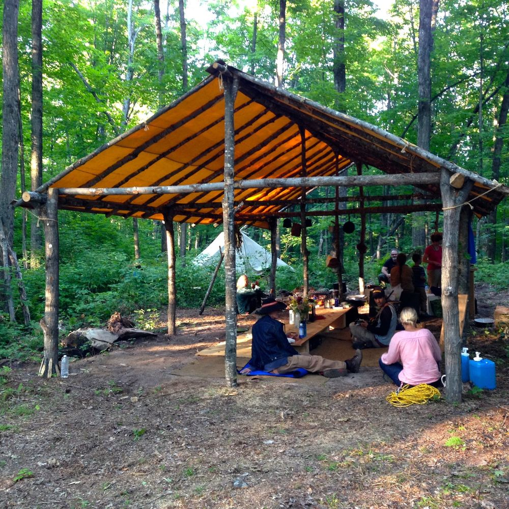 The community space had a table with ground seating. Toward the back is the cooking stove. We spent many hours here conversing, listening to live music, and sharing delicious, healthy meals. Jan and Rochelle's teepee is in the back.