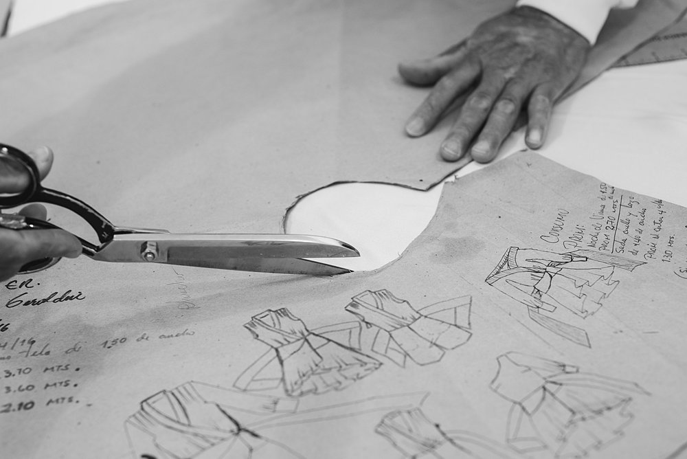 THE PATTERN - Now the pattern comes in stage. The pattern maker interpret a design with a practical understanding of garment construction. Held in place with weights, the garment's shape is drawn with absolute precision using chalk to trace the lines of the pattern.