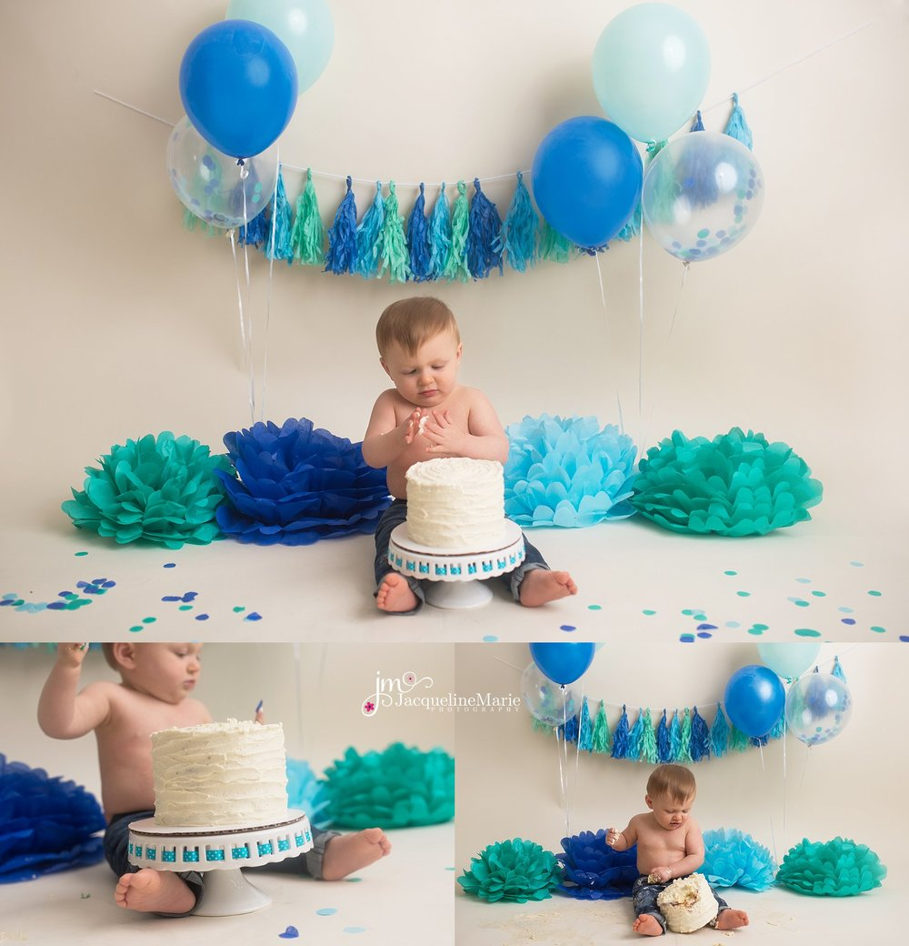 boy smashing birthday cake | cake smash photography Columbus Ohio | cake smash setup | cake smash photography | blue and teal cake smash | baby boy wearing jeans cake smash