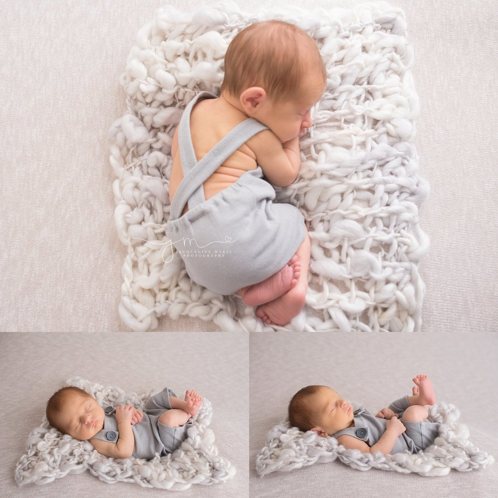 Newborn picture features baby boy wearing gray romper sleeping with legs crossed in Columbus Ohio