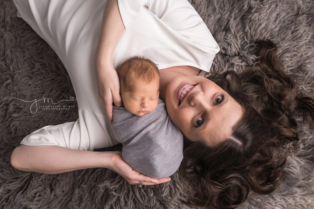 Newborn pictures features mother laying on rug holding baby boy in Columbus Ohio