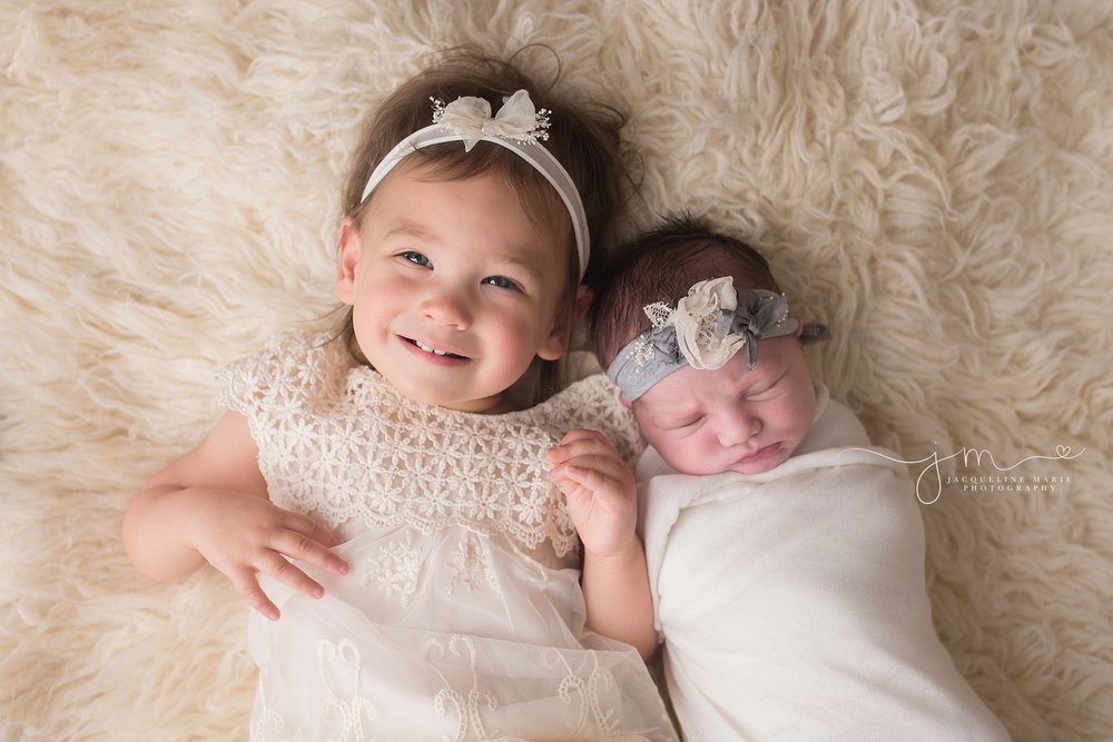 Older sister snuggles baby sister on cream fluffy rug in Columbus Ohio for newborn photography pictures