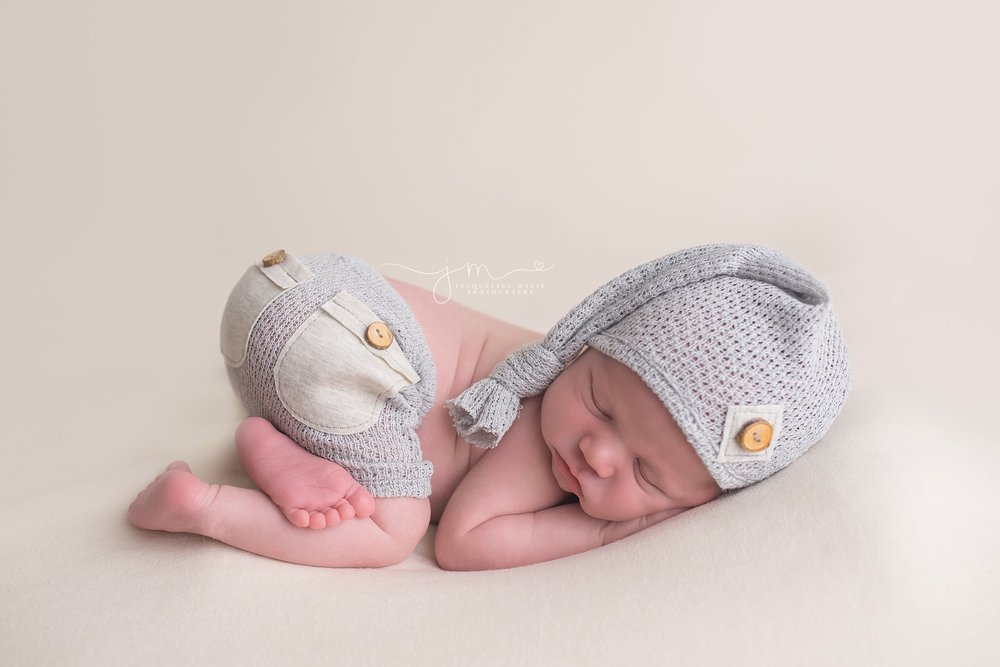Columbus Ohio newborn boy wears gray hat and matching bottoms for portrait at Jacqueline Marie Photography studio