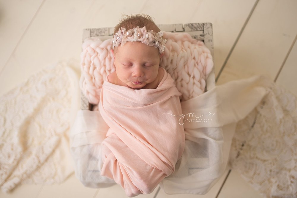 Newborn baby portrait features baby swaddled in pink wrap while sleeping in Columbus Ohio at Jacqueline Marie Photography